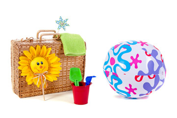 a wicker suitcase with beach ball and toys for a nice day at the