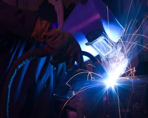Dramatic blue-lit MIG welding close