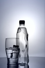 glass of cold mineral water with ice and plastic bottle