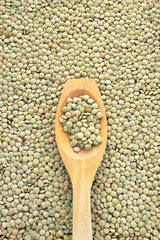 Wooden spoon and dried green lentils.