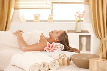 Young woman resting on massage bed at spa.