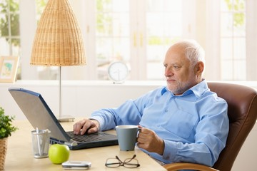 Elderly man using computer, having coffee