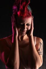 Frau verzieht schmerzlich das Gesicht und hält sich die Ohren zu