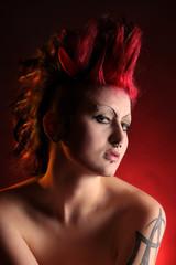 Coole Punkerin in rot mit kleinen Teufelshörnern