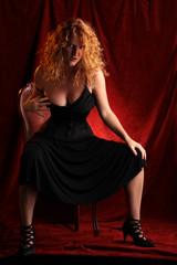 redhead striptease sitting on a chair