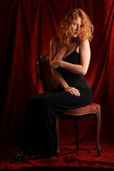 Rothaarige legt auf dem Stuhl sitzend eine Brust frei