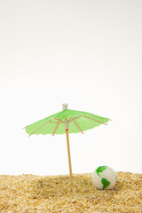 Green cocktail umbrella and glass globe