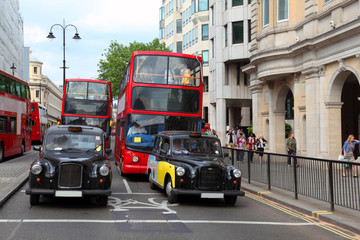 Red double-deckers with tourists and taxi on street of London