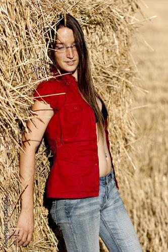Frau mit offener Bluse im Feld an Strohballen gelehnt