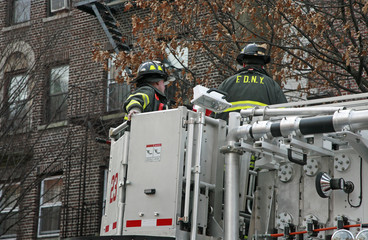 Firemen in bucket of ladder truck
