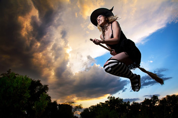 Flying witch in dramatic sky