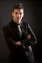 Fashion young businessman black suit casual tie on black backgro