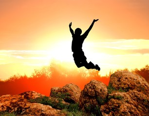 man silhouette jumping on a sunset background