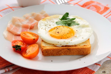 fried egg for breakfast with bacon and tomatoes