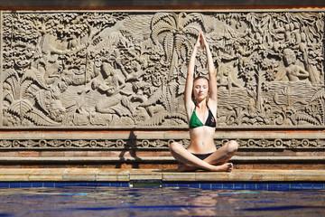 woman playing yoga beside the swimming pool in bali beach resort