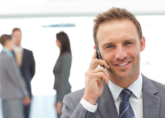 Happy businessman on the phone while his team working