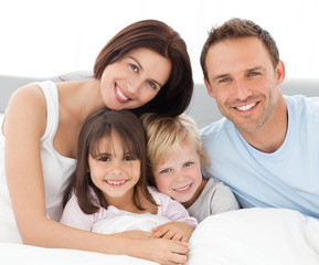 Wall Mural - Lovely family sitting together on the bed