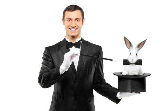 A magician in a black suit holding a top hat with a rabbit in it