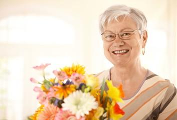 Portrait of happy senior woman with flowers