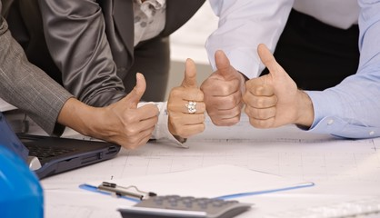 Closeup of 4 thumbs up in office