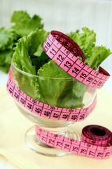 green salad  diet with a pink measuring tape
