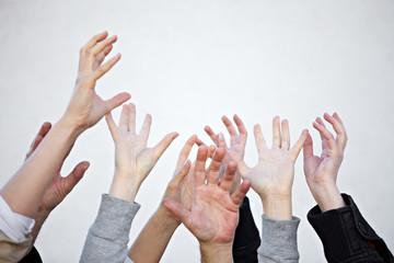 Viele Hände strecken sich