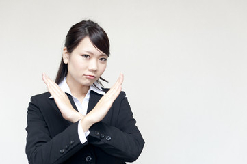 a portrait of young business woman showing x sign