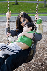 Mother swinging with disabled son with cerebral palsy
