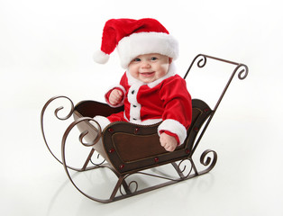 Smiling santa baby sitting in a sleigh