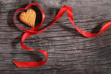 One cookies and heart shaped red ribbon
