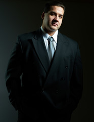 Dark portrait of handsome stylish young man in black suit