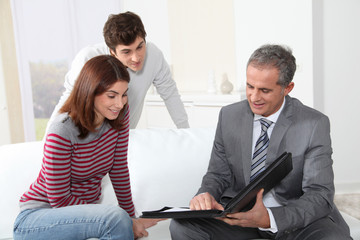 Young couple sigining renting contract with real estate agent