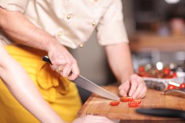 Koch schneidet Tomate