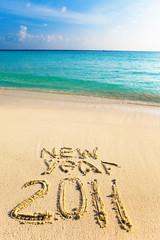 """On sand at ocean edge it is written """"2011"""""""