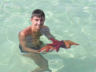 Man with 3 Starfishes in the Caribbean Sea