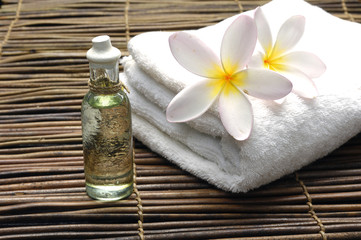 Zelfklevend Fotobehang Spa Frangipani on white towel with massage oil