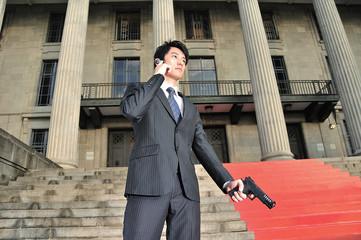 Asian Man with a Gun contacting HQ