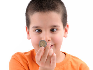 Cross-eyed kid looking at coin focused on coin.