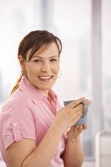 Happy office worker drinking tea