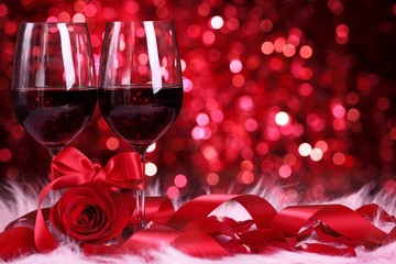 Two glasses of wine, rose and ribbon on abstract background.