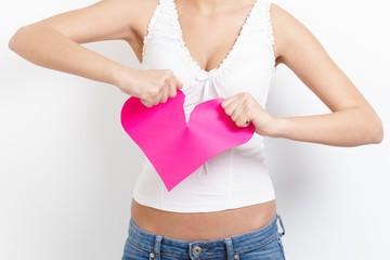 Heart-broken woman tearing paper heart