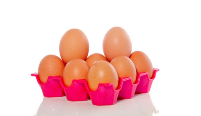 many brown eggs in a pink plastic tray isolated over white