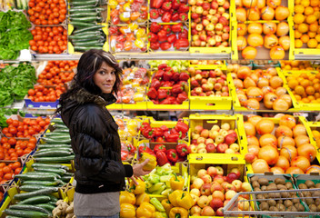 Beautiful young woman buying fruits and vegetables at a produce
