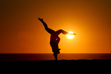 silhouette of gymnast in sunset on beach