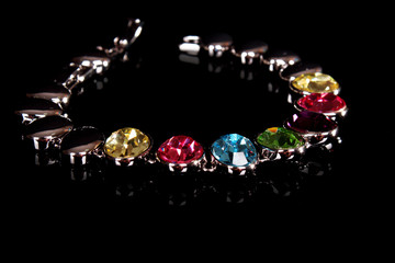 silver and diamonds bracelet with color  stones on black backgro