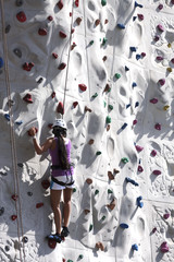 Woman in Putple Traversing Rock Wall