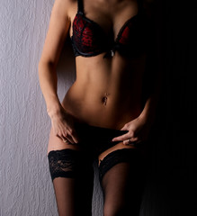 Sexy body of a young woman in dark red erotic lingerie