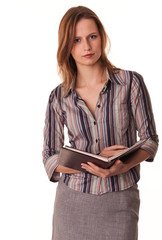 Serious confident young woman teacher holds textbook in her hand