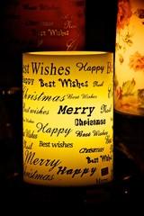 Weihnachtsgrüße international auf einer Kerze
