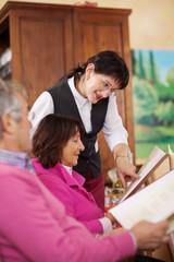 kellnerin berät gäste im restaurant